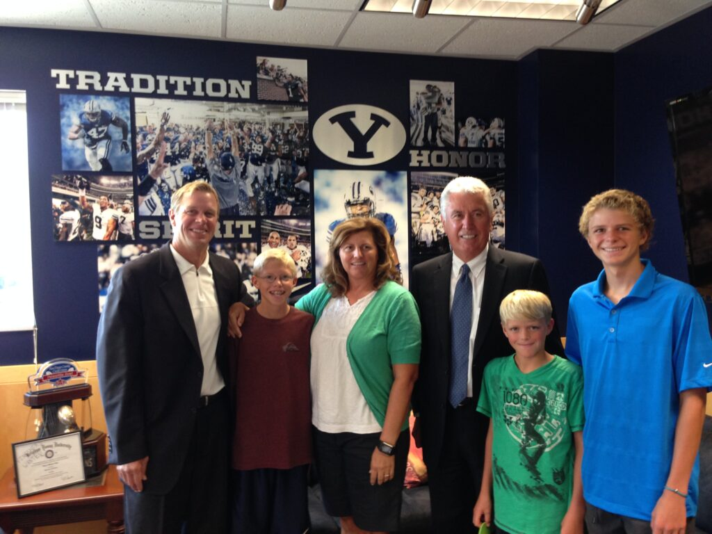 President Uchtdorf poses with Coach Bronco Mendenhall and family after visiting with the BYU football team on a recent trip to campus in conjunction with education week.
