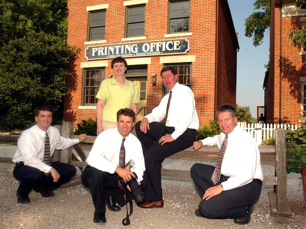 On June 25, 2002, members of the Church News staff and a Deseret News photographer posed outside the Printing Office in Old Nauvoo, where the Times and Seasons newspaper was published. Kneeling from left: Jason Swensen, Jeffrey D. Allred, R. Scott Lloyd. At back: Gerry Avant and Shaun Stahle.