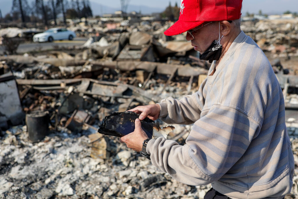 Leonard Sander holds a charred Book of Mormon found in the burned remnants of his home in the Medford Estates neighborhood of Medford, Oregon, on Monday, Sept. 21, 2020. Sander's home was one of at least 2,357 homes burned in the Almeda Fire.