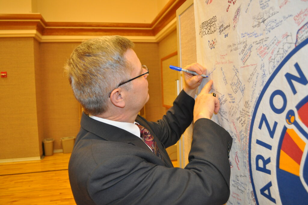 Tracy Watson of the Missionary Department adds his signature on flag, along with missionaries serving in the Arizona Phoenix Mission, after a multi-zone conference in Phoenix, Arizona, in March 2012.
