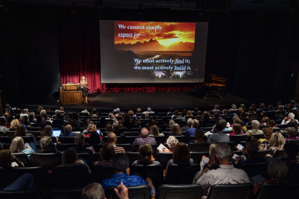 """Faculty member Carrie M. Wrigley speaks on """"Finding Joy, No Matter What the Circumstances"""" inside the Pardoe Theatre during BYU Education Week in Provo on Tuesday, Aug. 17, 2021."""