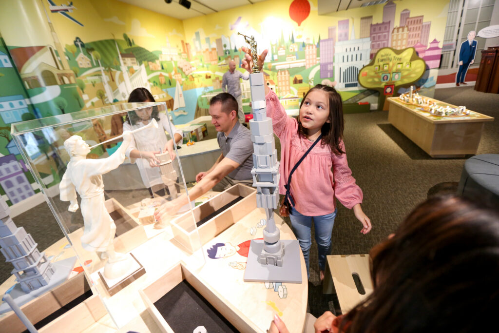 """Kaylee Tabla, 9, builds a model of a temple during a sneak peek of """"Temples Dot the Earth,"""" a new exhibit at The Church of Jesus Christ of Latter-day Saints' Church History Museum in Salt Lake City on Saturday, Feb. 8, 2020."""