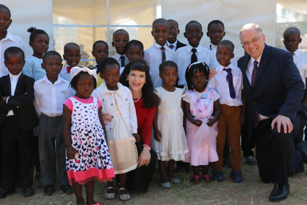 Elder Neil L. Andersen of the Quorum of the Twelve Apostles, right, and Sister Kathy Andersen, center, gather with children after a member meeting in Zimbabwe on Nov. 18. 2018.