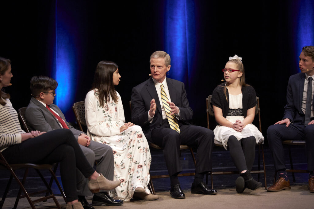 Elder David A. Bednar of the Quorum of the Twelve Apostles interacts during a panel discussion of youth and young single adult participants at the 2020 Temple and Family History Leadership Instruction meeting Feb., 27, 2020, at the Conference Center Theater in Salt Lake City.