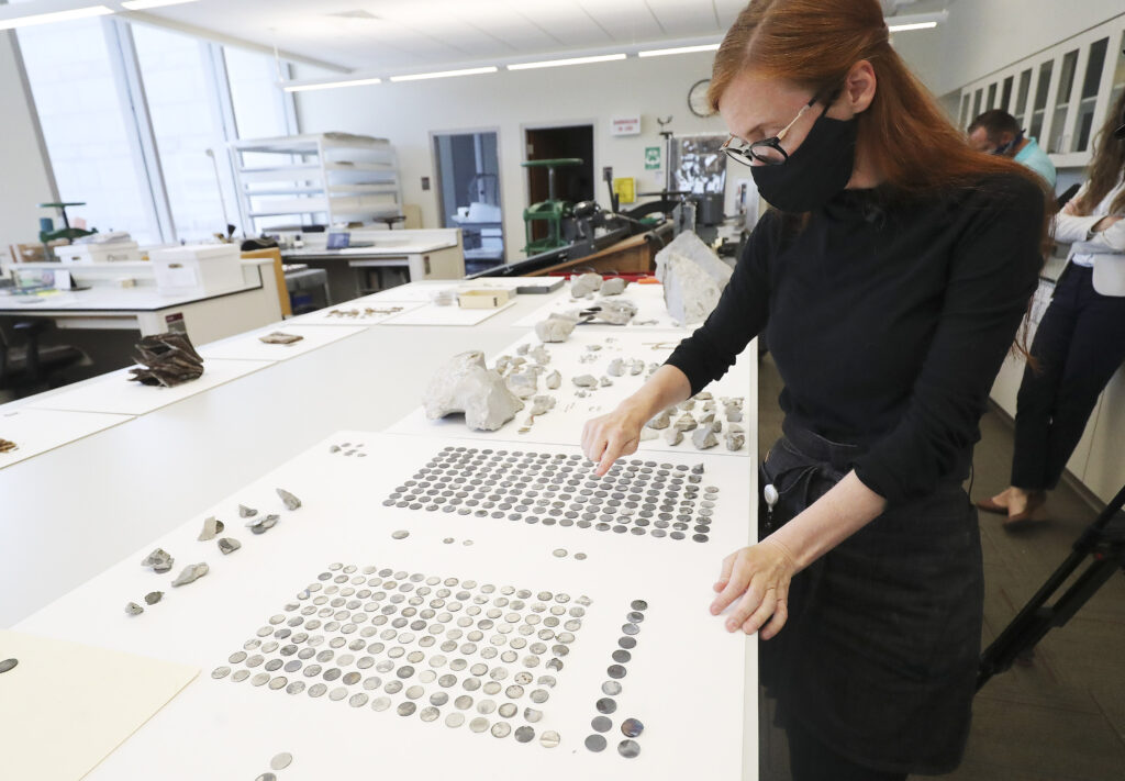 Emiline Twitchell, conservator at the Church History Library, looks over coins found in the Salt Lake Temple capstone and time capsule at the Church History Library in Salt Lake City on Tuesday, July 14, 2020.