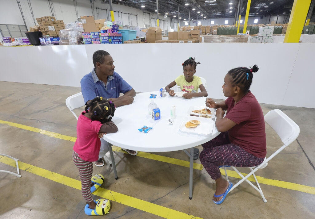 Haitian refugees Nadege LaFrance, left, talks with his wife, Evenor Elisca, and their children while eating at the Family Transfer Center in Houston on Monday, June 7, 2021. The center provides a temporary respite for families who have been cleared at the U.S. border and need short-term shelter and food. The creation of the Family Transfer Center is the result of a collaboration between The Church of Jesus Christ of Latter-day Saints, Catholic Charities, the National Association of Christian Churches, YMCA International Services, Texas Adventist Community Services, Houston Responds and The Houston Food Bank.