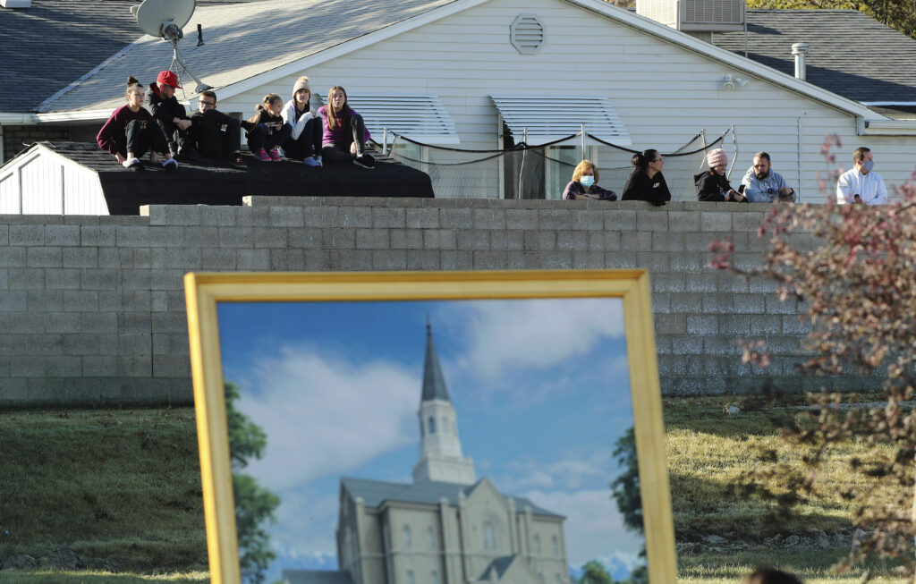 Onlookers watch over a fence during a groundbreaking ceremony for the Taylorsville Utah Temple in Taylorsville on Saturday, Oct. 31, 2020.
