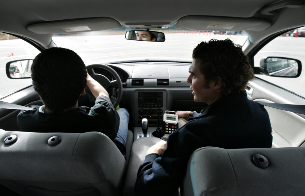 An instructor, right, explains how to drive safely to a high school sophomore as he drives during a driver's education class in Midvale, Utah, on Tuesday, Dec. 2, 2008.