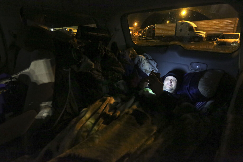 Jesse Kinman looks at his phone before going to sleep in his van, outside of Walmart in Puyallup, Wash., on Sunday, Jan. 26, 2020. Kinman has been homeless for most of his adult life. He struggled with alcohol and a meth addiction for more than 18 years, but is now clean and sober.