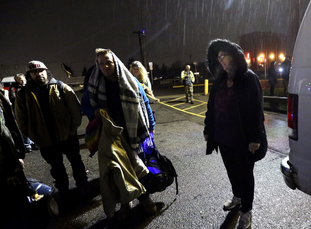 Diane Kienholz, right, picks up homeless people to drive them to Puyallup Nazarene Church so they can sleep for the night in Puyallup, Wash., on Sunday, Jan. 26, 2020.