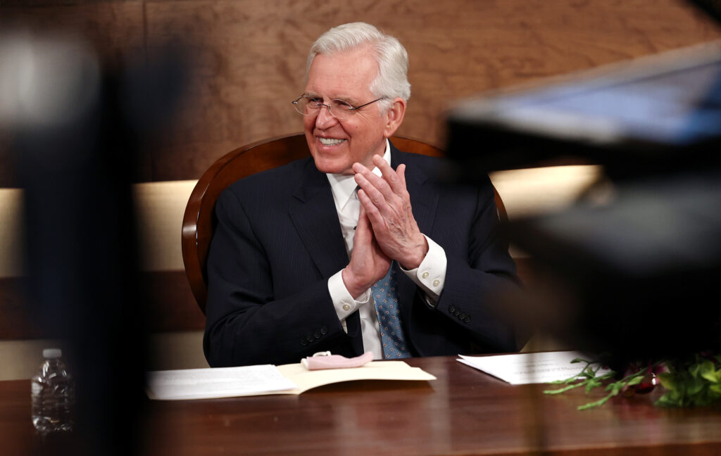Elder D. Todd Christofferson of the Quorum of the Twelve Apostles quietly applauds after his wife, Sister Kathy Christofferson completed her talk in Spanish for a March 14 Spanish-language young adult devotional that was taped at the Church Office Building in Salt Lake City on Friday, Feb. 26, 2021.