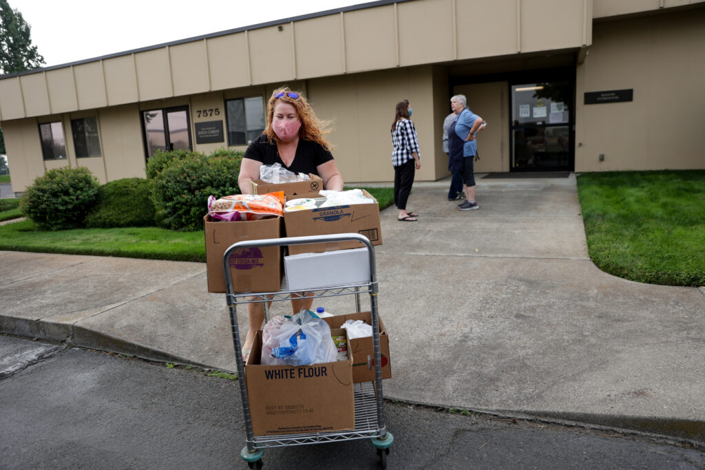 Bear Creek Ward Relief Society President Deni Goodwin takes food orders to her car at the Bishop's Storehouse in Medford, Oregon, before delivering them to the homes of members on Monday, Sept. 21, 2020.