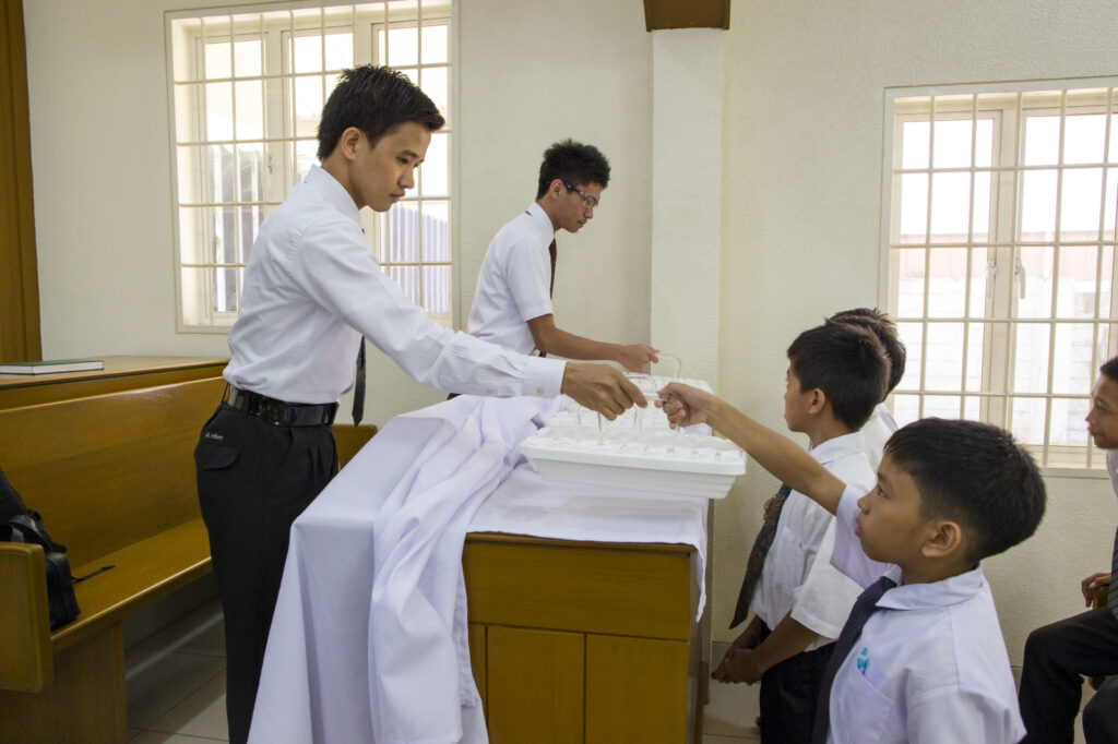 A group of young men in the Philippines bless and pass the sacrament in the chapel.