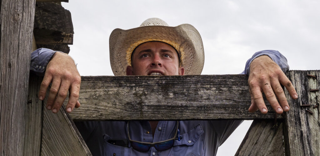 Billy Bevers leans on a gate as he talks to others as they work to get cattle sorted and loaded for transport at Deseret Ranches in St. Cloud, Florida, on Tuesday, Aug. 24, 2021.