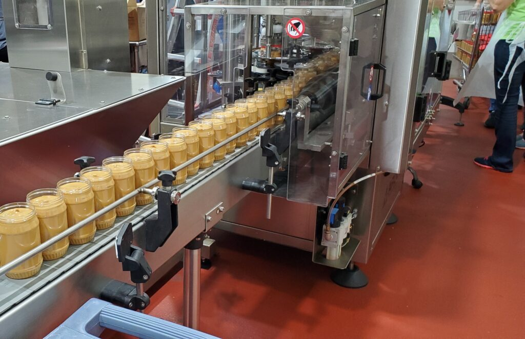 Jars of peanut butter move through the production line to be sealed and capped with lids at the Church's peanut butter cannery in Houston, Texas, on Oct. 23, 2020.