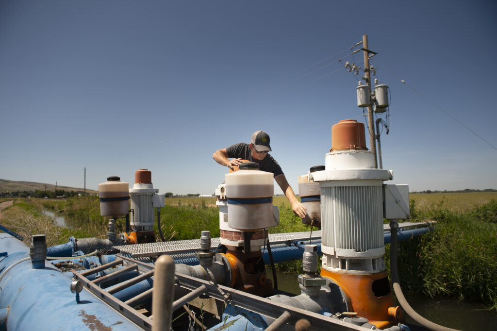 Elder Garrett Mill checks the oil on a pump during his shift Saturday, July 18, 2020, at Idaho Falls Crops, a welfare farm of The Church of Jesus Christ of Latter-day Saints south of Idaho Falls, Idaho.