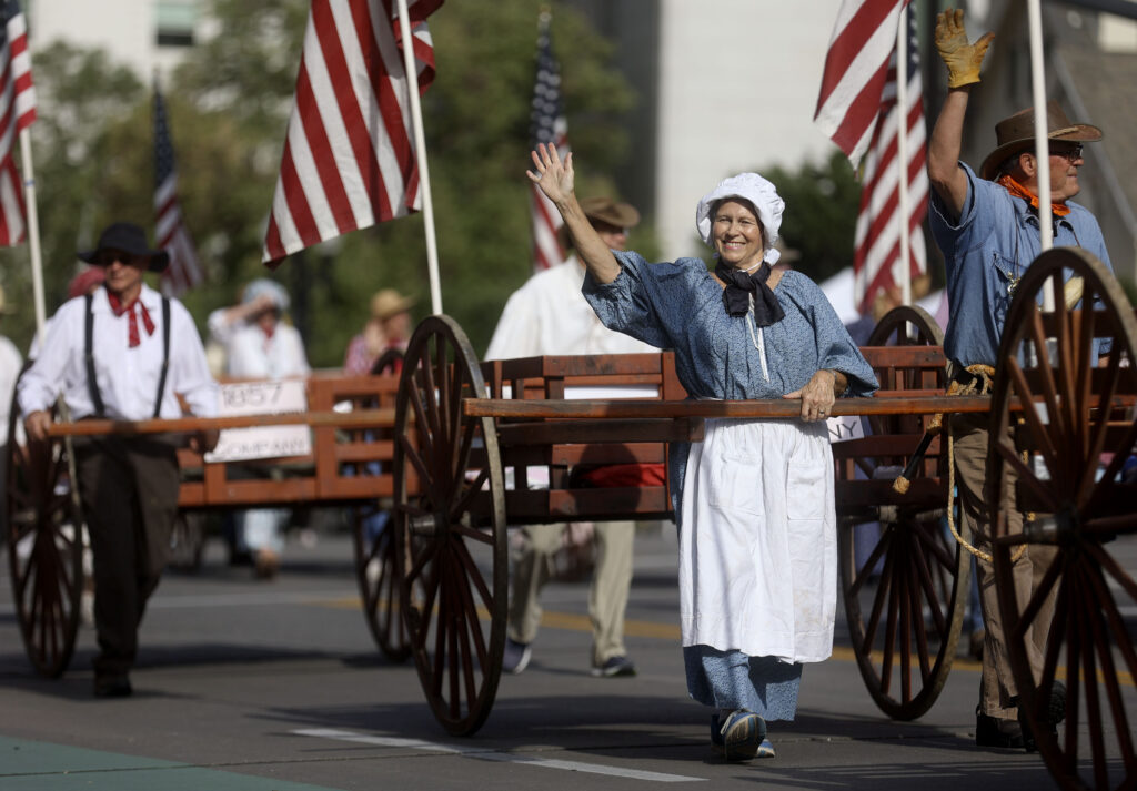 A woman marches with the Sons of Utah Pioneers in the Days of '47 Parade in Salt Lake City on Friday, July 23, 2021.