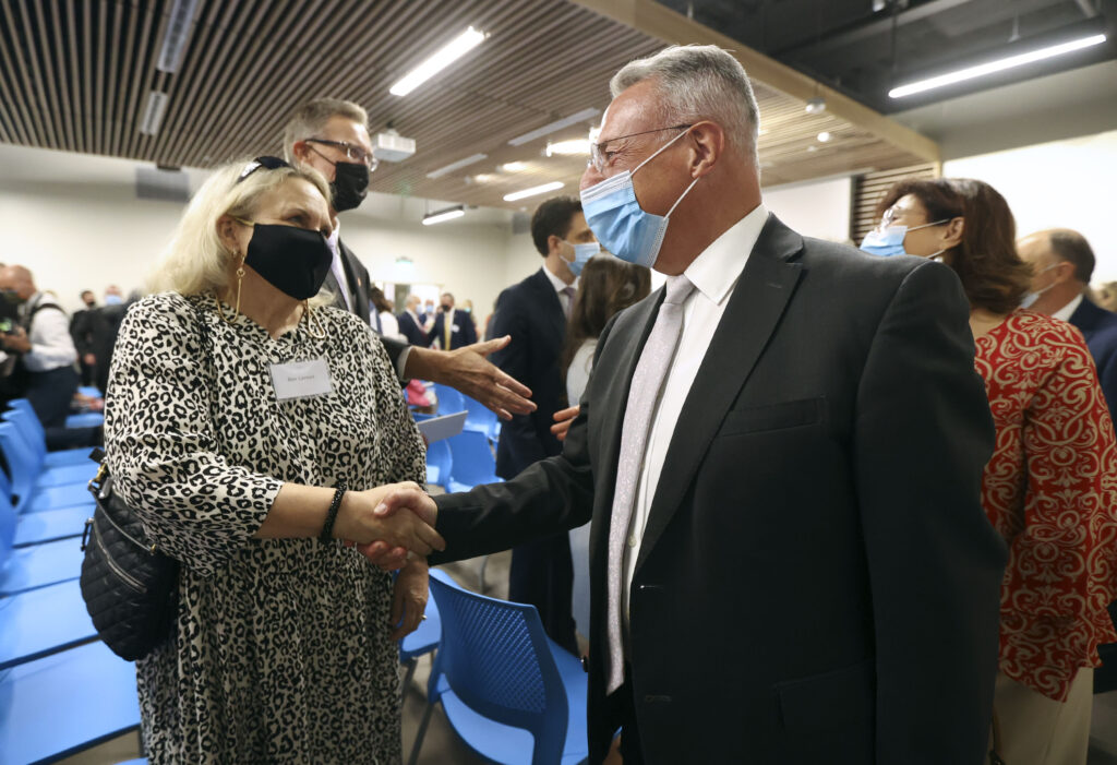 Elder Ulisses Soares of the Quorum of the Twelve Apostles shakes hands with Bev Larsen at the dedication ceremony for the Mesa Arizona Temple Visitors' Center in Mesa, Ariz., on Thursday, Aug. 12, 2021.