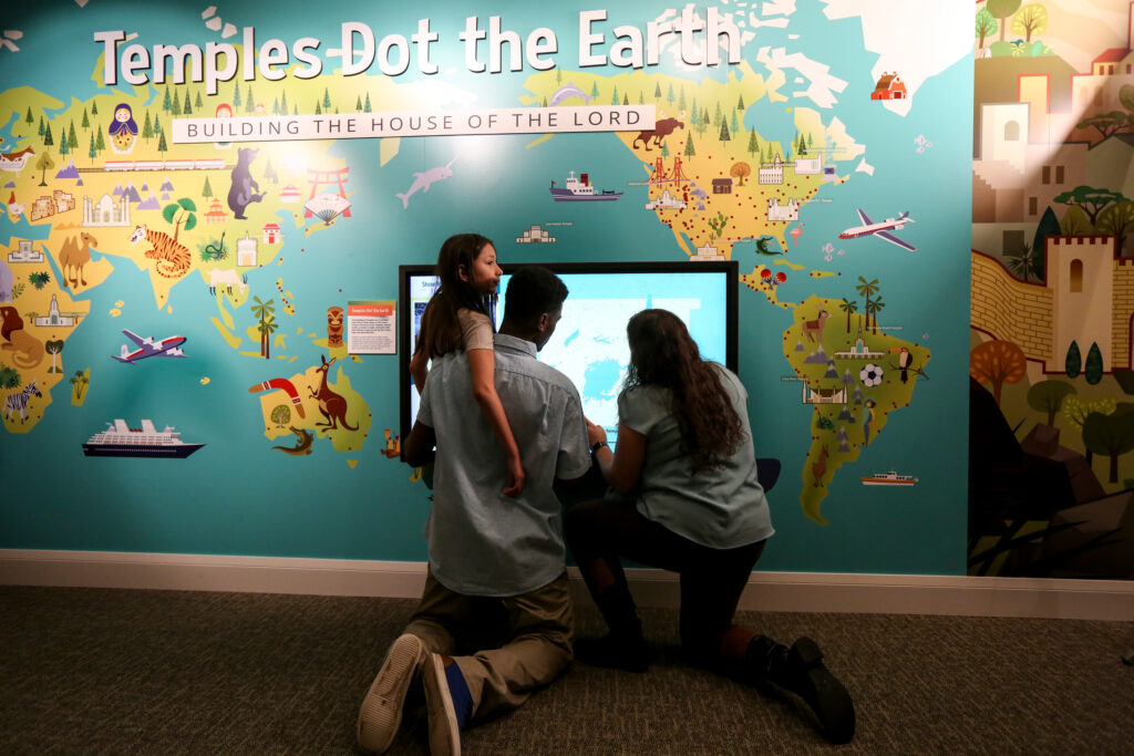 """Ligia Stewart, 10, left, Jerome (no last name given) and Ligia's mother, also named Ligia, get a sneak peek of """"Temples Dot the Earth,"""" a new exhibit at The Church of Jesus Christ of Latter-day Saints' Church History Museum in Salt Lake City on Saturday, Feb. 8, 2020."""