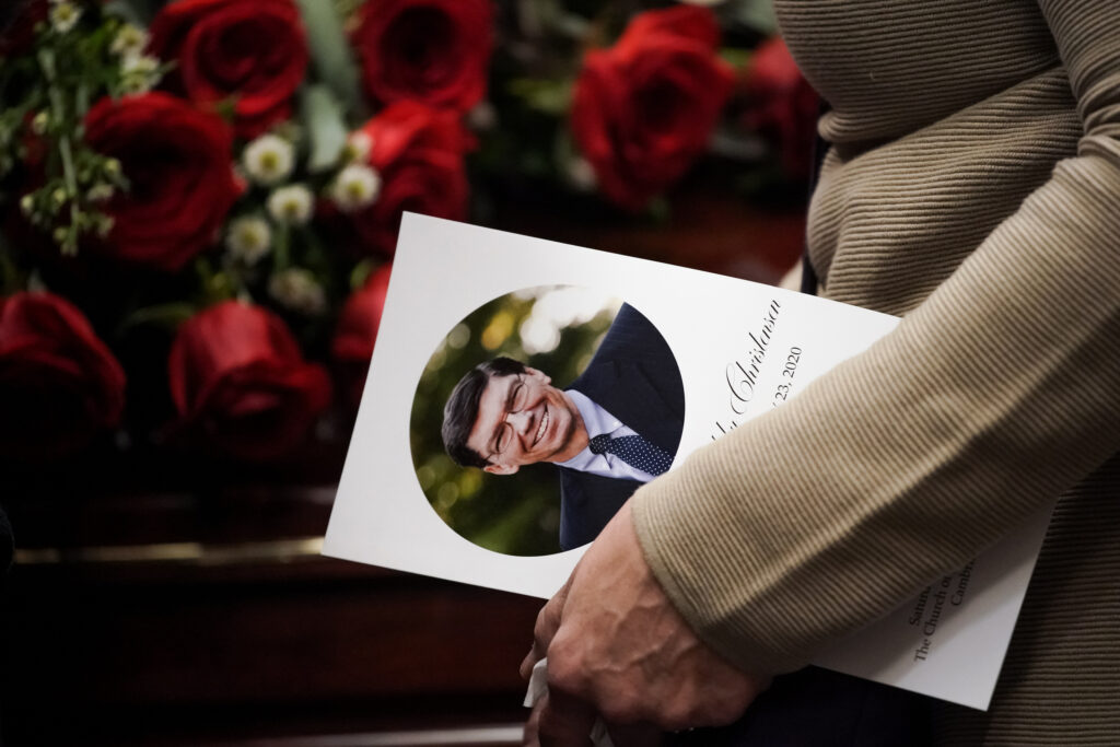 A mourner carries a program during a viewing before the funeral of Clayton Christensen at a Cambridge, Massachusetts chapel of The Church of Jesus Christ of Latter-day Saints on Saturday, Feb. 1, 2020.