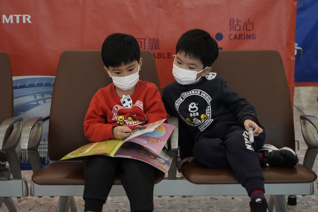 Passengers wear masks to prevent an outbreak of a new coronavirus in the high speed train station, in Hong Kong, Wednesday, Jan. 22, 2020.