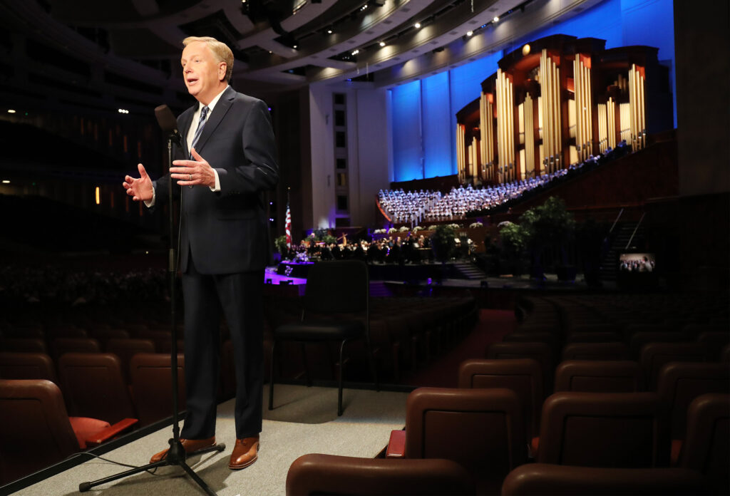 """Lloyd Newell speaks as the Tabernacle Choir at Temple Square performs """"Music & the Spoken Word"""" and celebrates its 90th anniversary, in Salt Lake City on Sunday, July 14, 2019."""