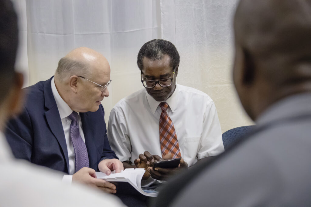 Elder Dale G. Renlund looks through a manual with a member in Dominica during the apostle's visit to the Caribbean Area on Feb. 16, 2020.