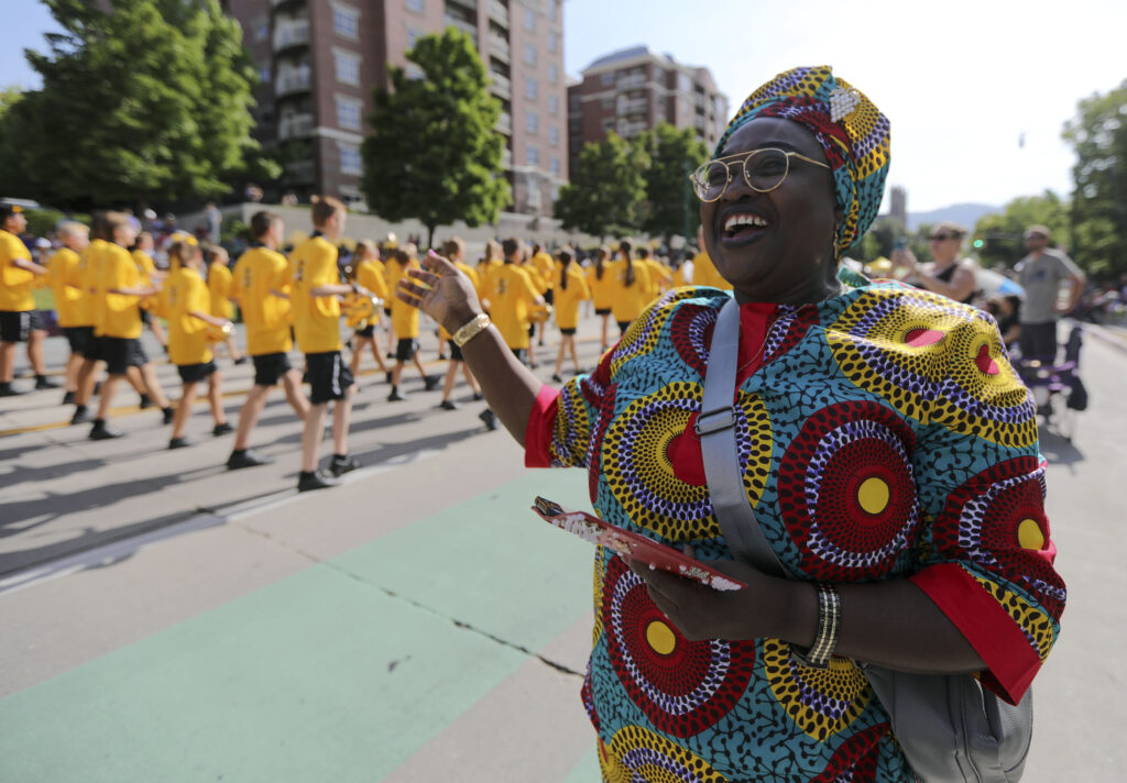 Cariama Kallon-Olayemi dances and sings as a marching band passes by during the Days of '47 Parade in Salt Lake City on Friday, July 23, 2021.
