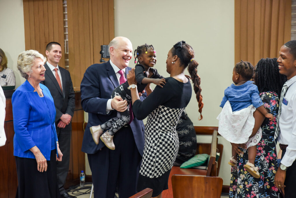 Elder Dale G. Renlund hands a child to her mother following a leadership training in Kingston, Jamaica, on Feb. 22, 2020. The apostle visited the island as part of the Caribbean Area annual review.