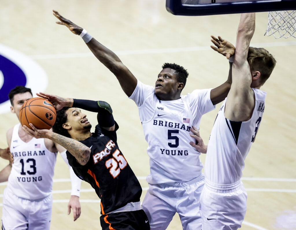 Pacific Tigers guard Justin Moore (25) goes to the hoop against Brigham Young Cougars forwards Gideon George (5) and Matt Haarms (3) at the Marriott Center in Provo, Utah, on Saturday, Jan. 30, 2021.